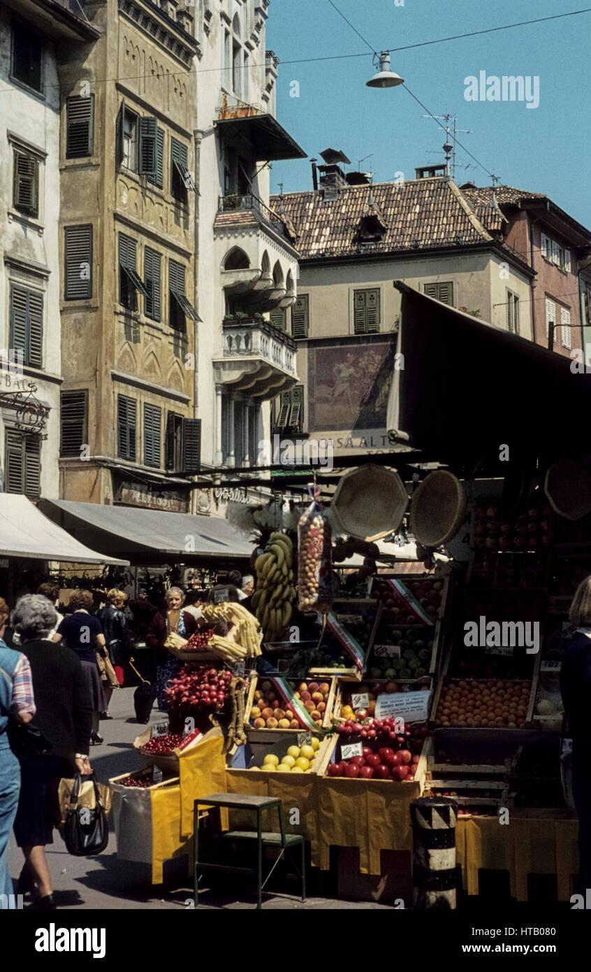 Market in Bolzano in the seventies, 1977. Obstmarkt in Bozen in 1970igern. Marktstände mit Häuserfassade. - Stock Image