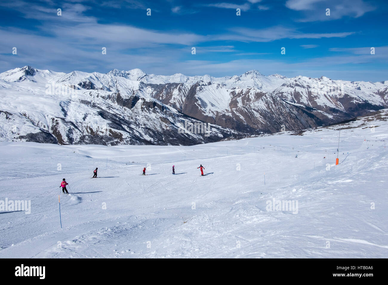 Piste at Meribel, Three Valleys ski resort in the French Alps, on a sunny winters day, with five skiers on the piste - Stock Image