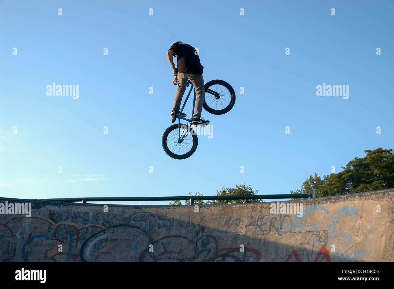 BMX biker leaps high against a blue sky. - Stock Image