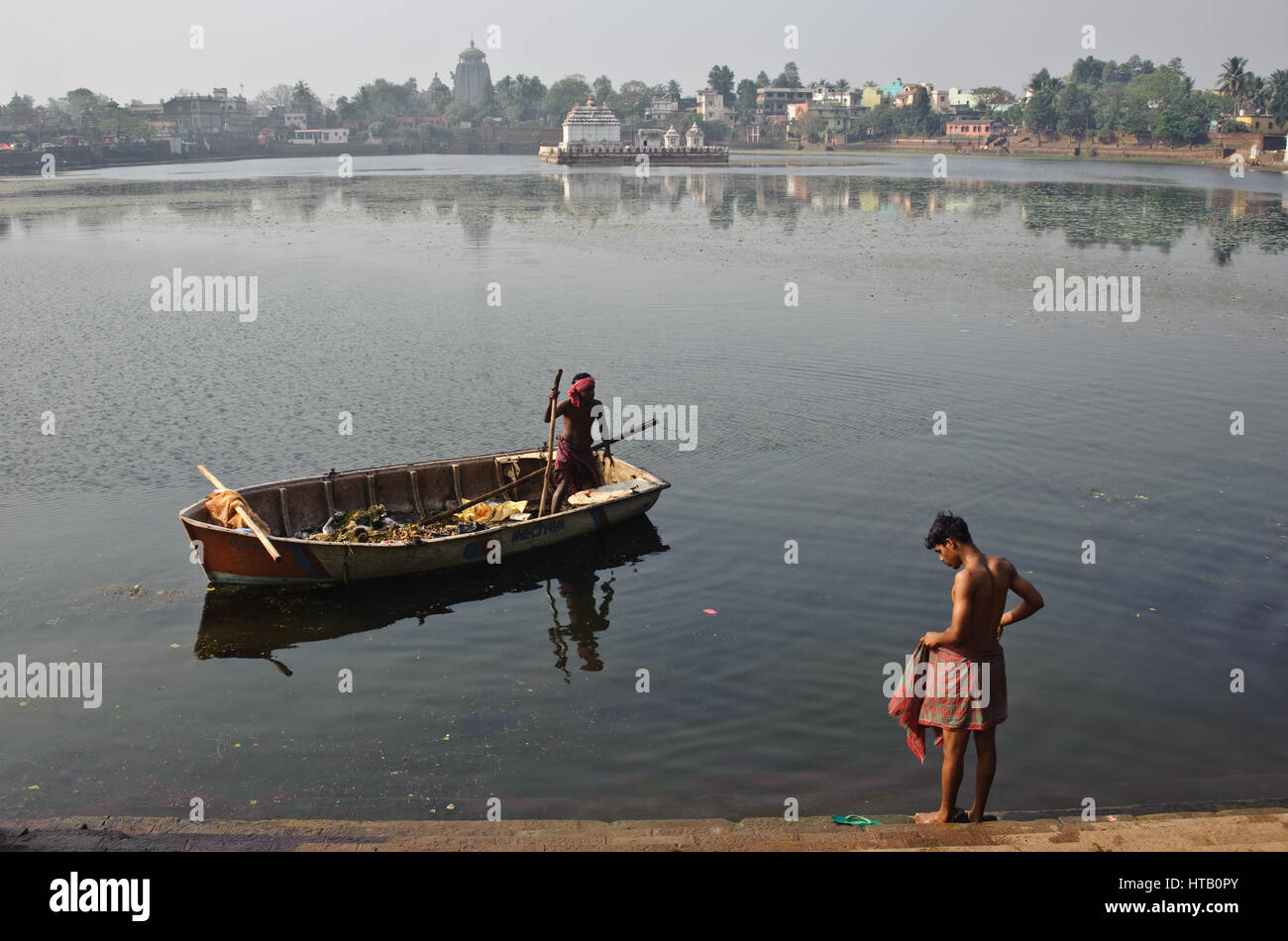 Cleaning up the lake 'bindu sagar' + young man ready to bathe in the lake ( India) In the background, the - Stock Image