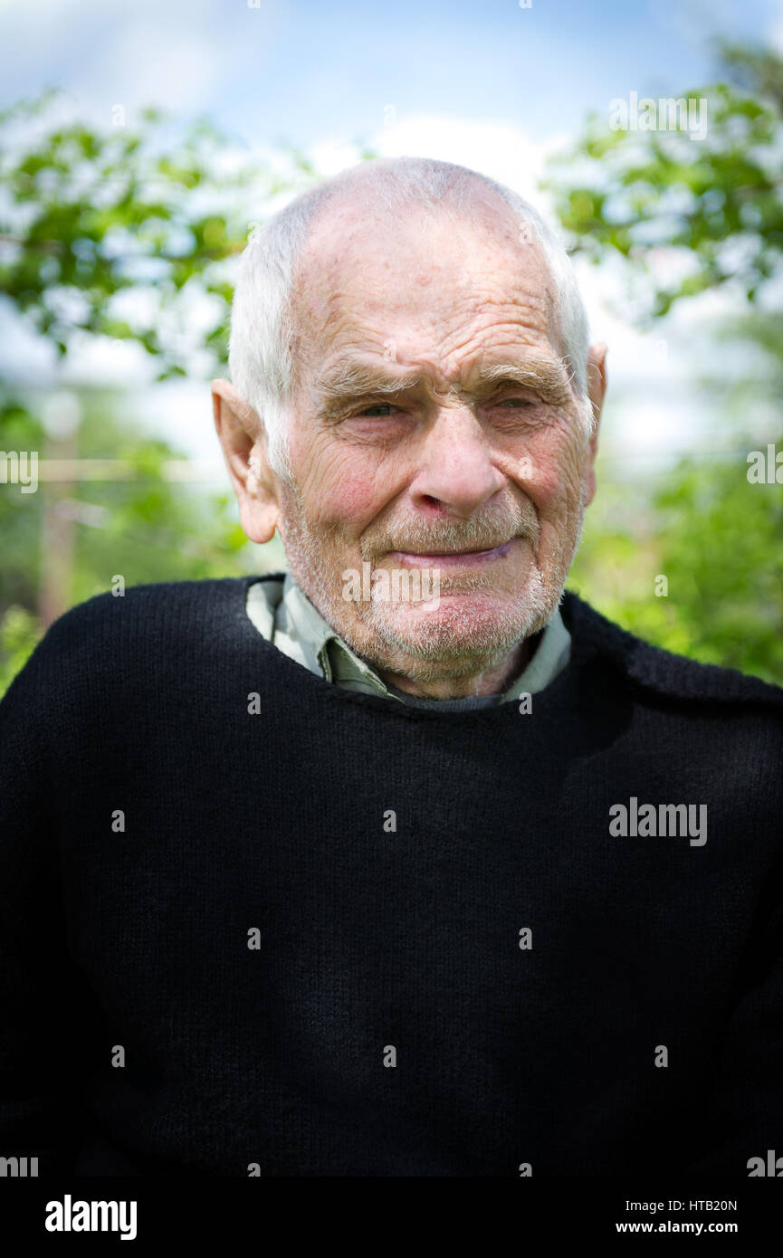 Handsome 80 plus year old senior man posing for a portrait in his garden. - Stock Image