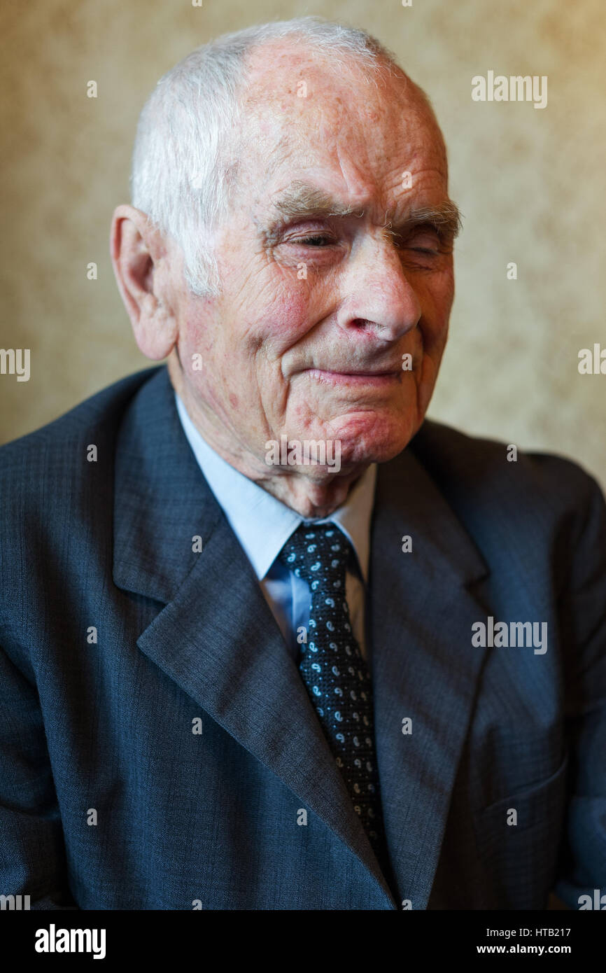 Handsome 80 plus year old senior man posing for a portrait in his house. - Stock Image