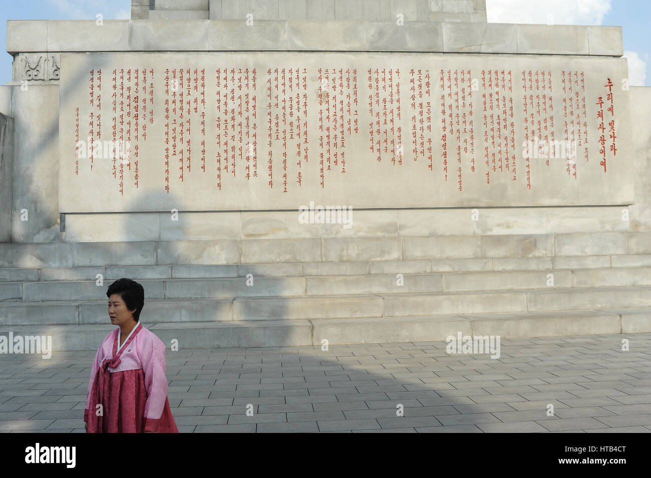 08.08.2012, Pyongyang, North Korea - A North Korean woman wearing a traditional dress is seen at the pedestal of - Stock Image
