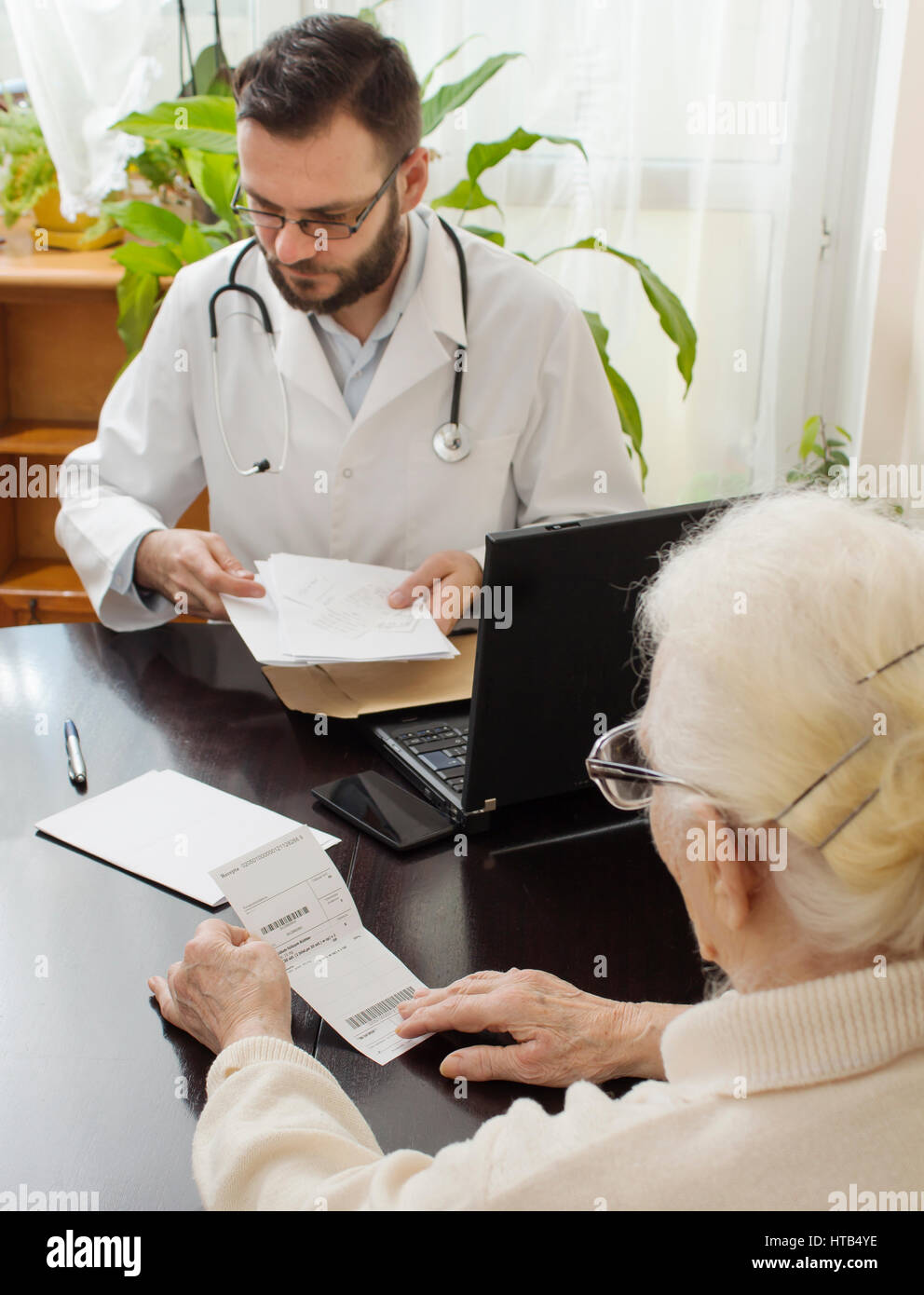 geriatrician doctor with a patient in his office. Old woman at the doctor geriatrician. - Stock Image