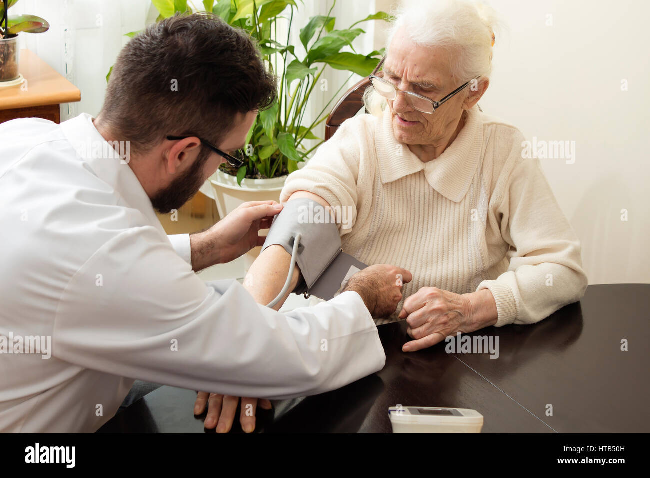 A private doctor's office. Geriatrician doctor takes the patient and measure her blood pressure. - Stock Image