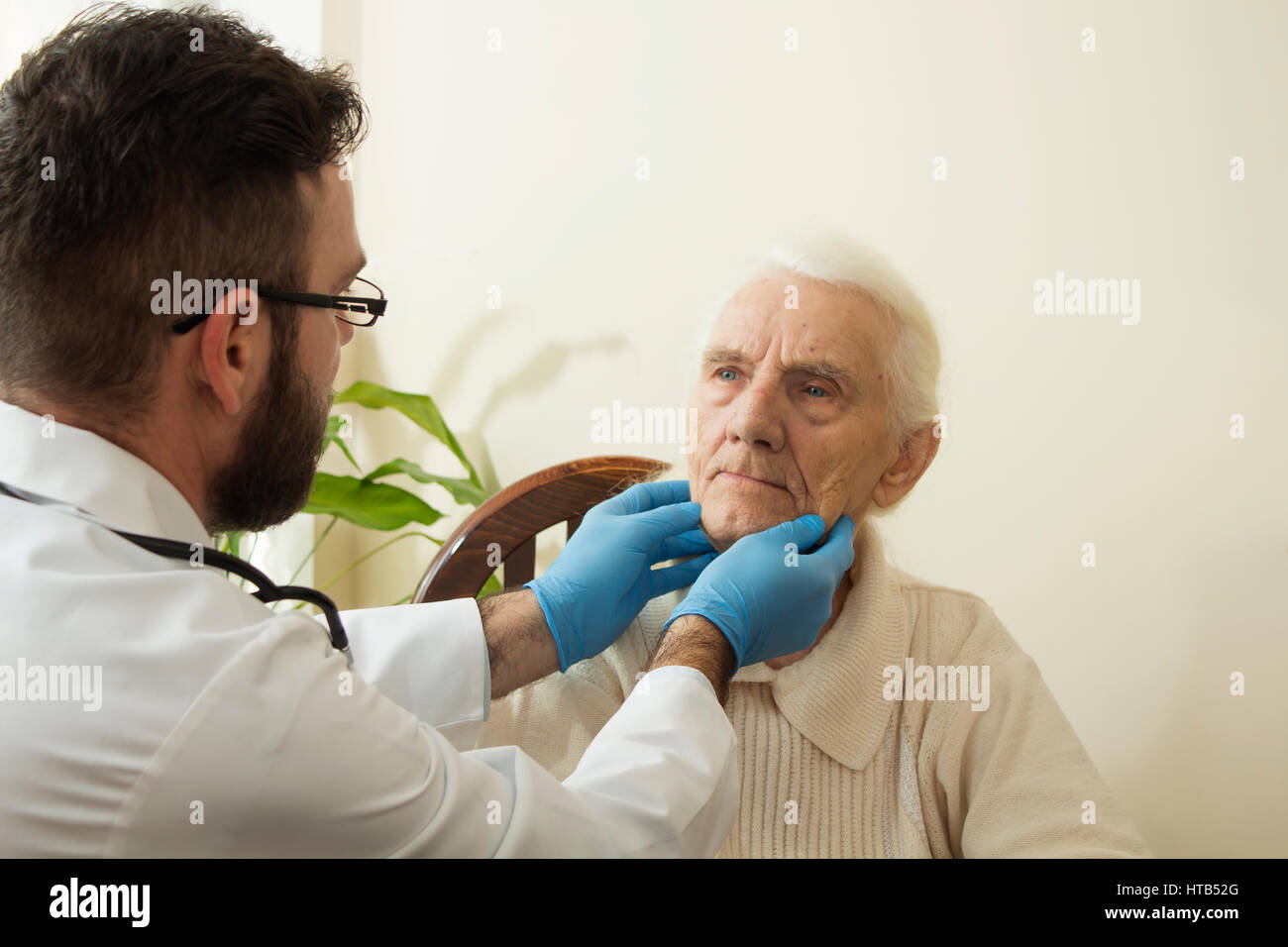 The doctor examines the lymph nodes on the neck of an old woman. - Stock Image