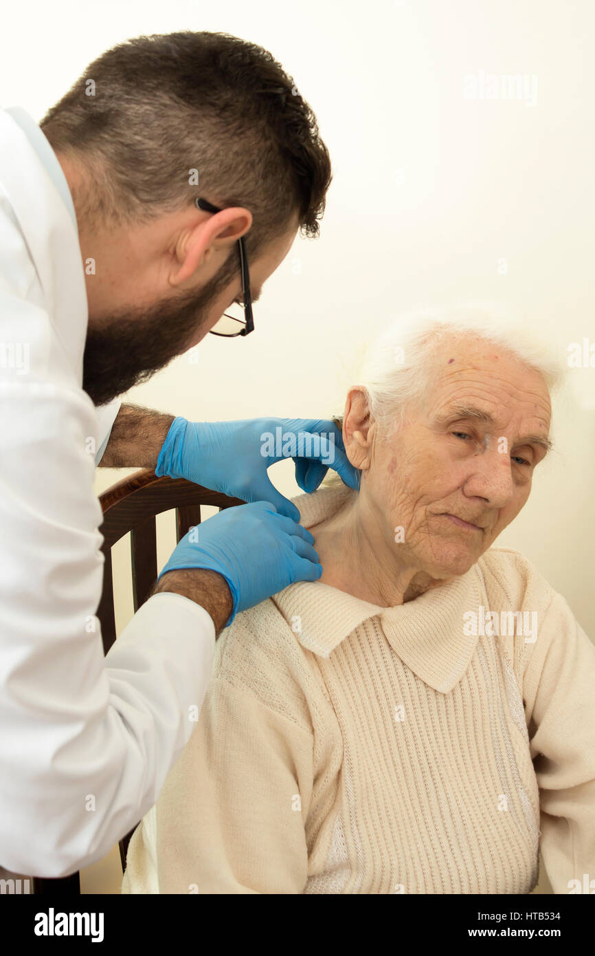 The doctor geriatrician during the test. Doctor examines changes in the skin of an old woman. - Stock Image