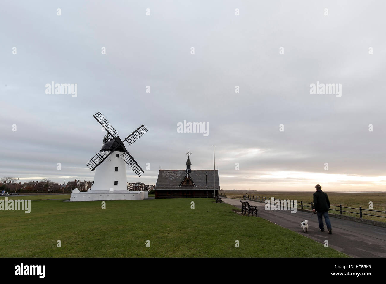 Lytham Windmill is situated on Lytham Green in the coastal town of Lytham St Annes, Lancashire, England. A man walks - Stock Image