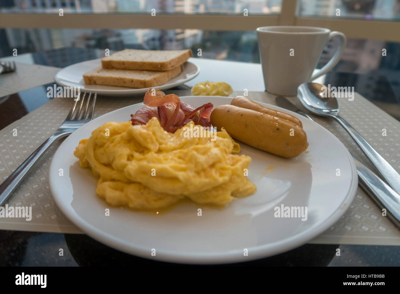 Breakfast with scambled eggs, sausage and bacon - Stock Image