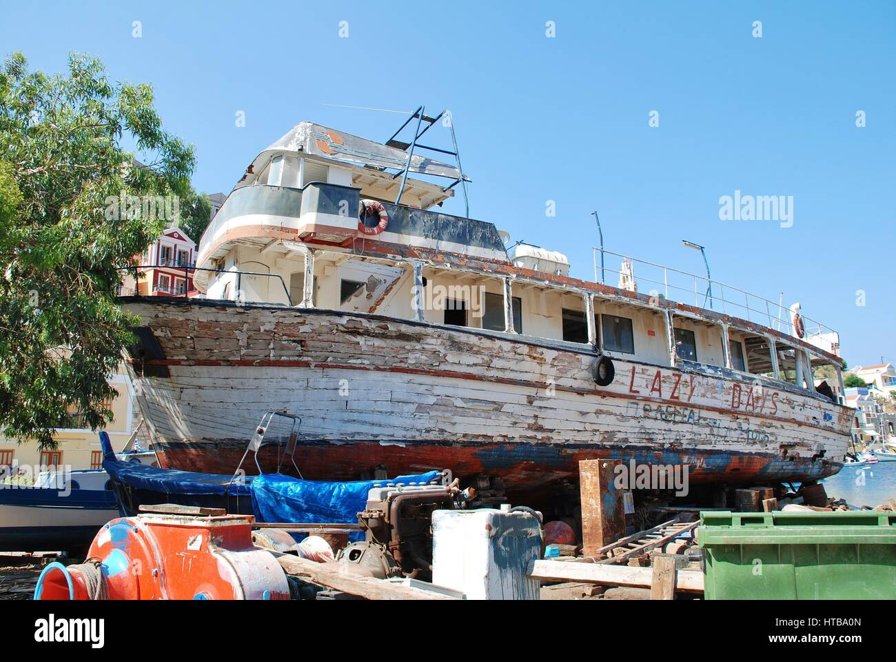 The crumbling remains of former excursion boat Lazy Days in the boat yard at Yialos on the Greek island of Symi. - Stock Image