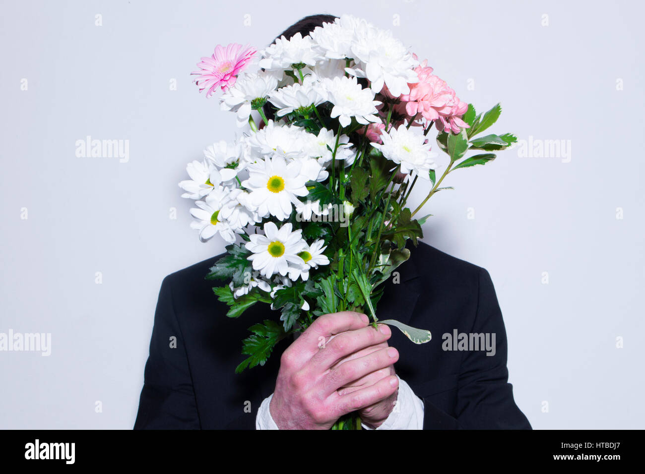 A man hiding his face with flowers stock photo 135476495 alamy a man hiding his face with flowers izmirmasajfo Image collections
