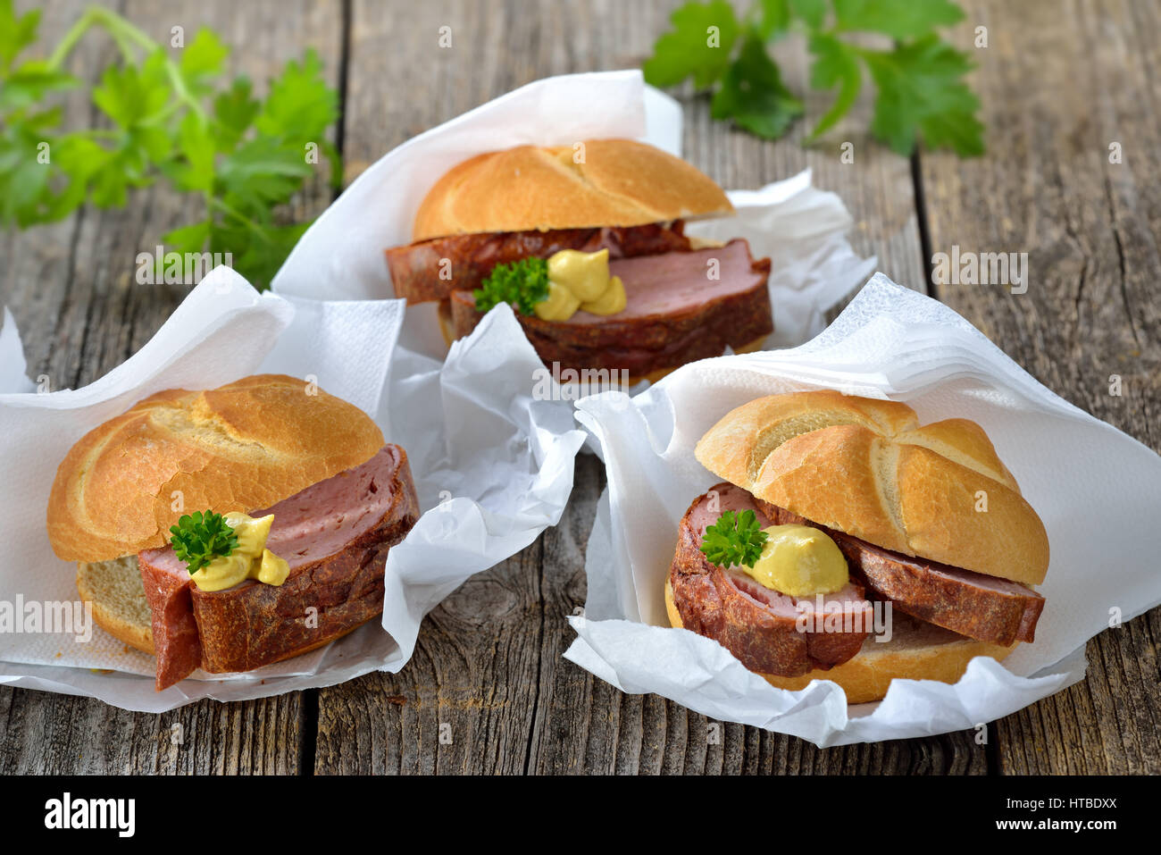 Bavarian takeaway food: Three rolls with baked meat loaf and mustard on wrapping paper with a napkin Stock Photo