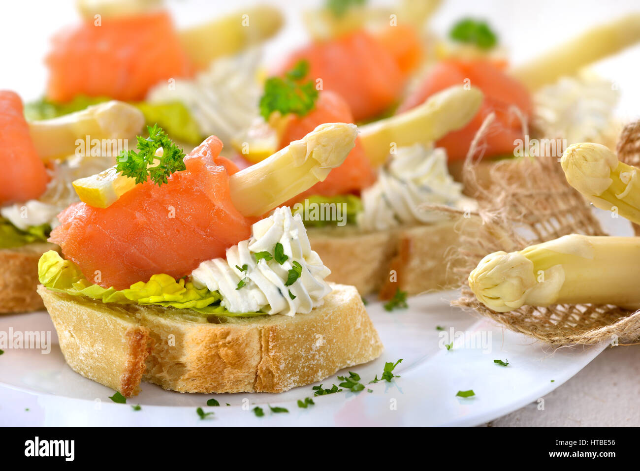 Delicious canapes with German white asparagus, cream cheese with herbs, smoked salmon on Italian ciabatta bread - Stock Image