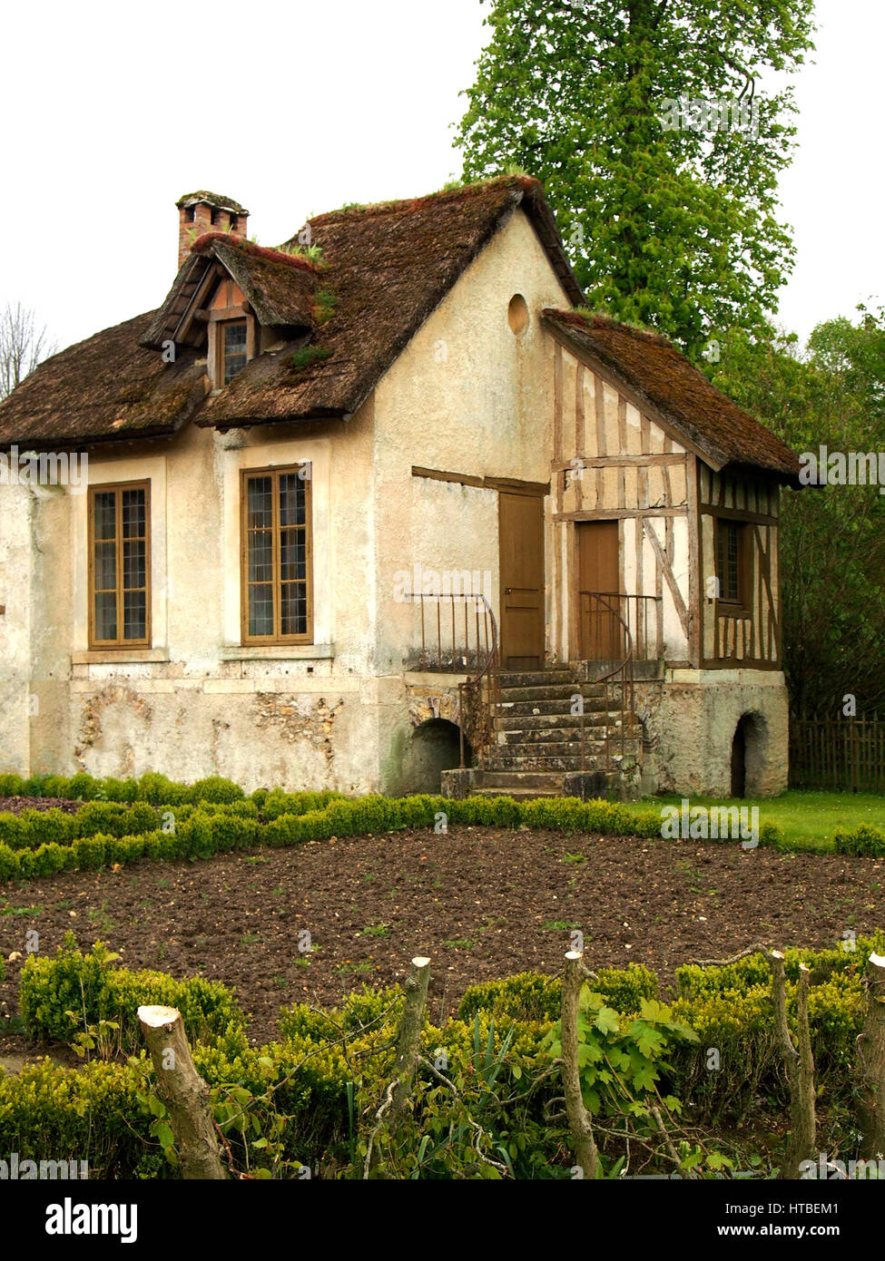 A traditional French cottage with a small garden and a thatched roof ...