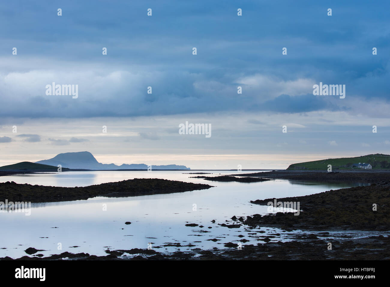 A solitary cottage on the shore of Clew Bay with Clare Island beyond, Co Mayo, Ireland - Stock Image