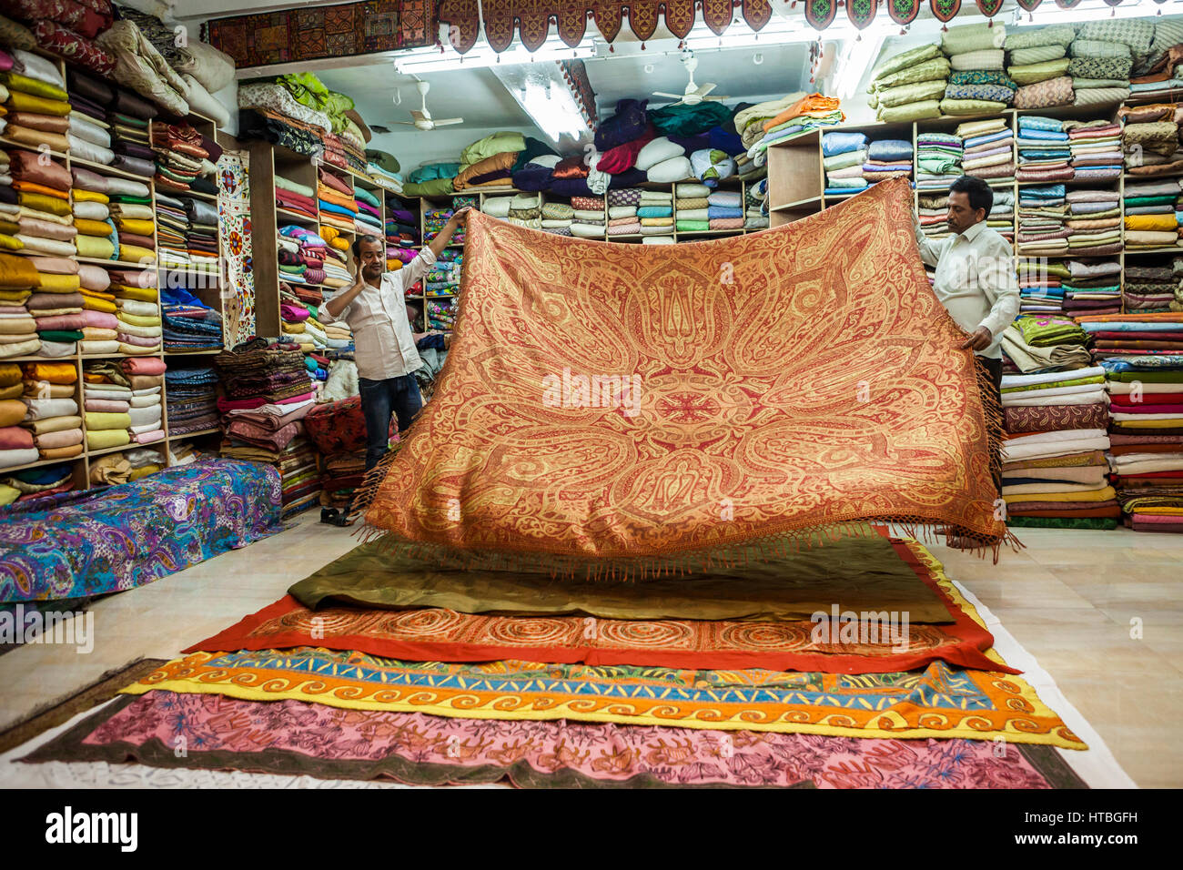 Two men in a showroom laying out different textiles / blankets for customers to see and buy, Jodhpur, Rajasthan, - Stock Image