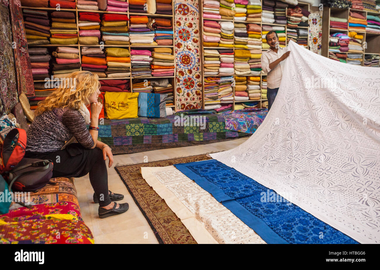 A woman sits and views textiles being shown by a salesman in a show room, Jodhpur, Rajasthan, India. - Stock Image