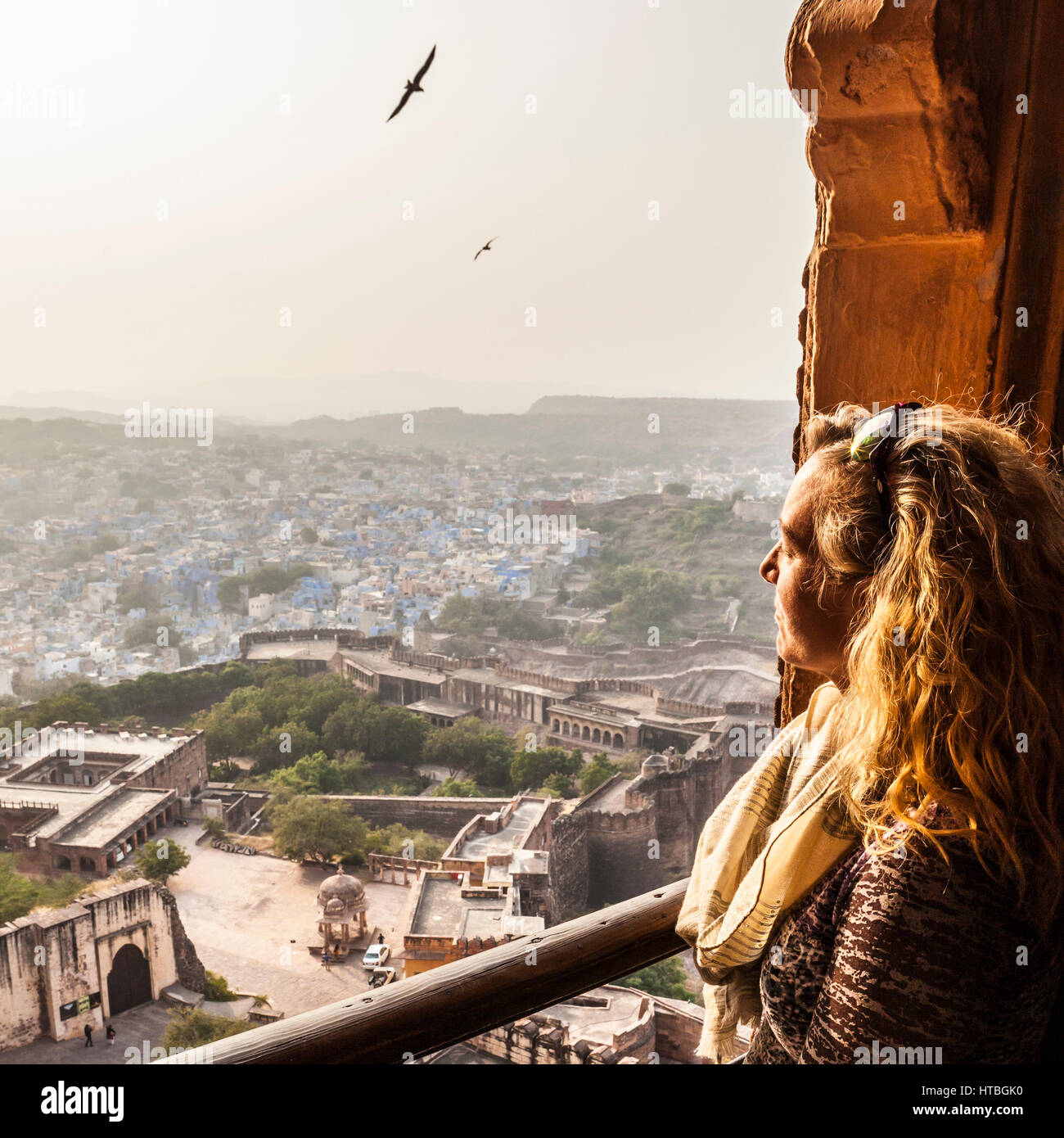 A woman looks out over the city of Jodhpur from a window high in Mehrangarh Fort. Rajasthan, India. - Stock Image