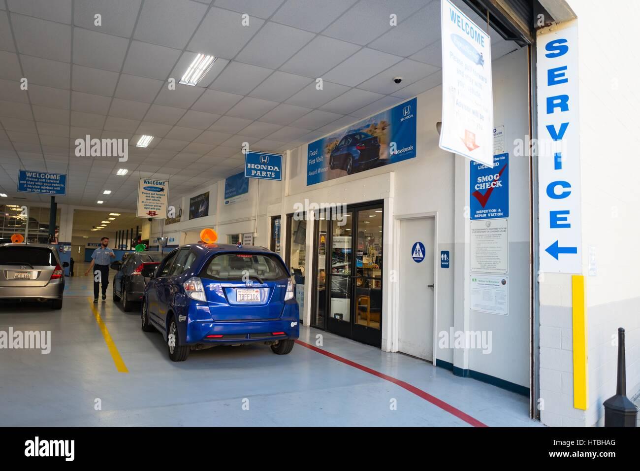 A compact Honda automobile pulls into the service center of a Honda