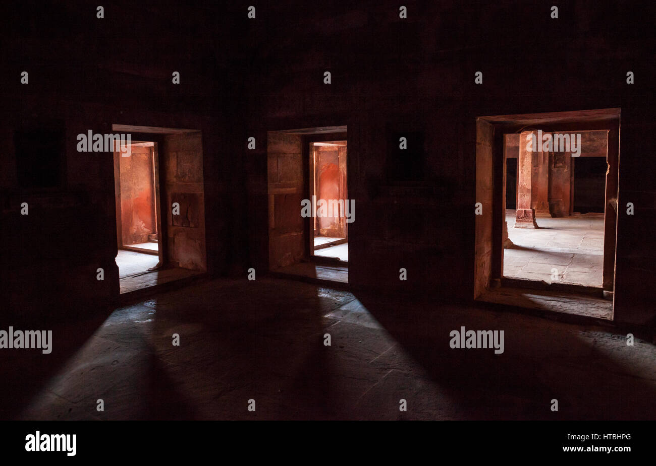 Three doorways in a dark room, Fatehpur Sikri, Uttar Pradesh, India. - Stock Image