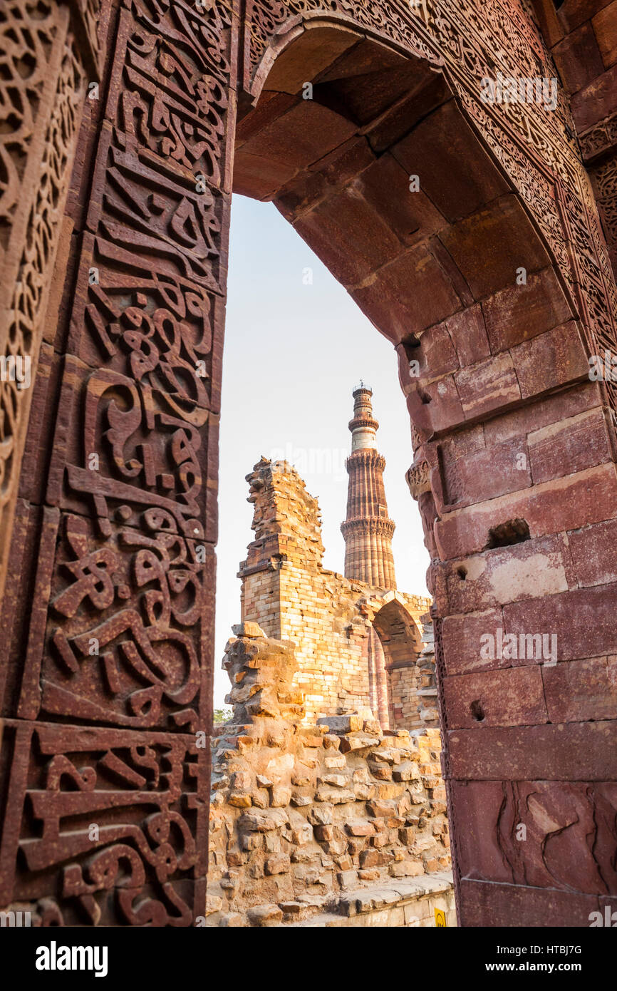 The ruins of Qutb complex with Qutb Minar in the background, Delhi, India. - Stock Image