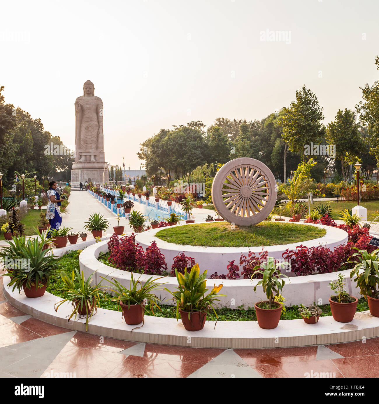 A view of the Ashoka Chakra / dharma wheel, walkway, and gardens surrounding the standing Buddha at the Thai temple - Stock Image