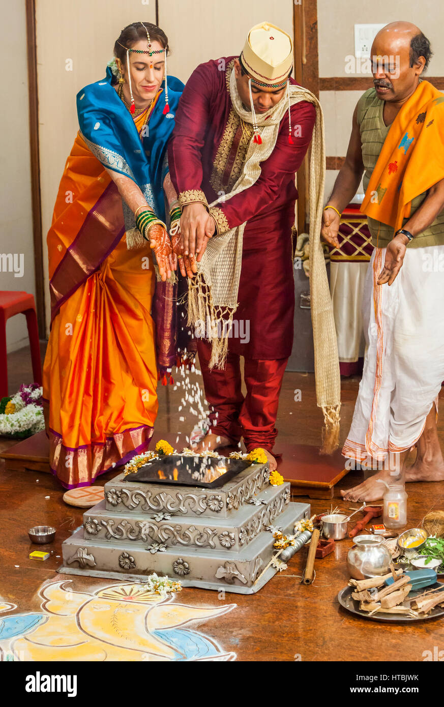 The bride and groom at an Indian wedding making offerings of puffed rice to the holy fire accompanied by the priest. - Stock Image
