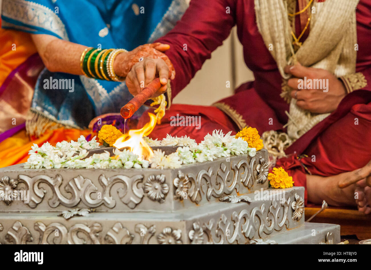 7f5321e58f9e1 The bride and groom at a Indian wedding making offerings of oil to the holy  fire