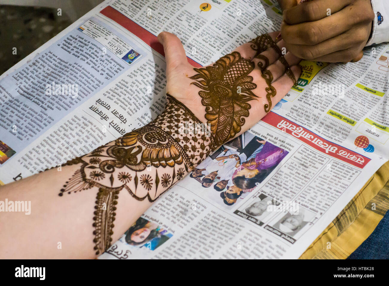 Henna being applied to a womans arm, hand, and fingers by a Mehndi artist in preparation for a wedding ceremony. - Stock Image