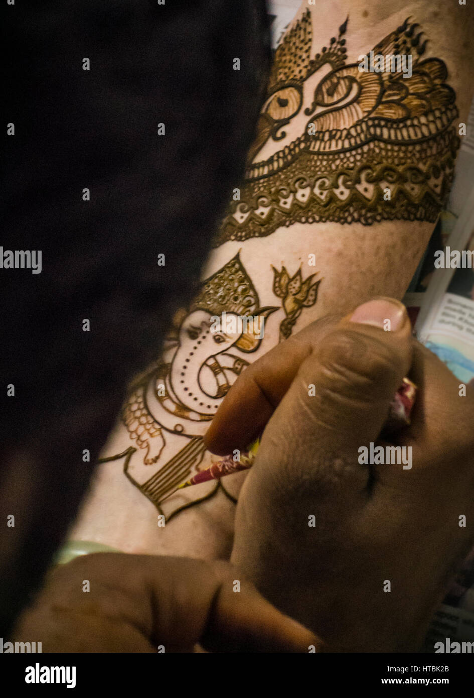 A Henna / Mehndi artist working on a bride's arm during a Henna party. The Elephant figure is Ganesha, one of - Stock Image