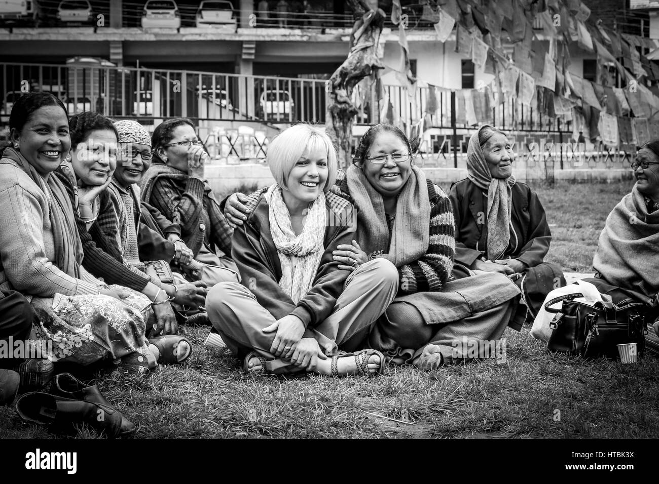Tibetan women sitting with tourist smiling - Stock Image