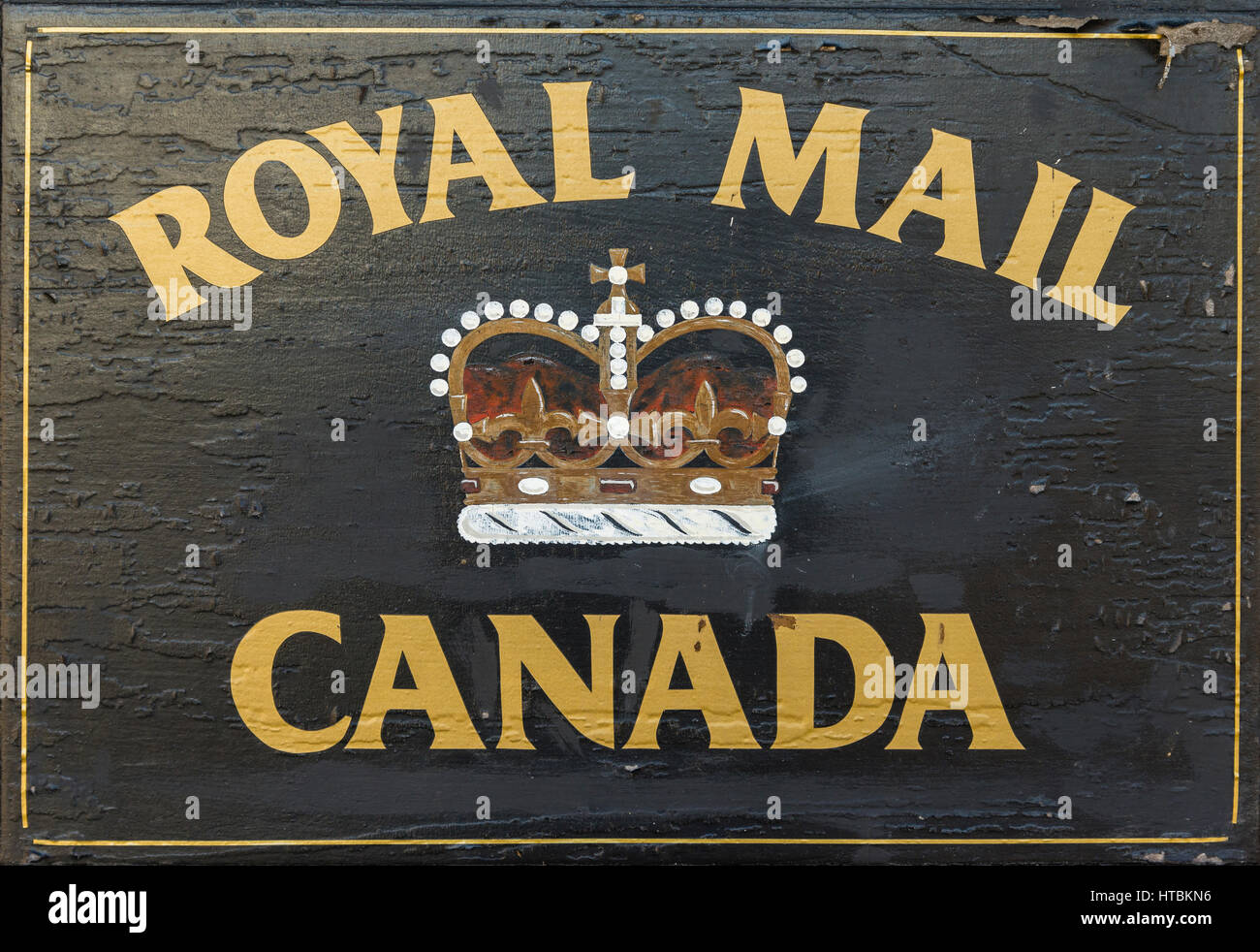 A black Royal Mail Canada sign with gold lettering with a crown in the center. - Stock Image