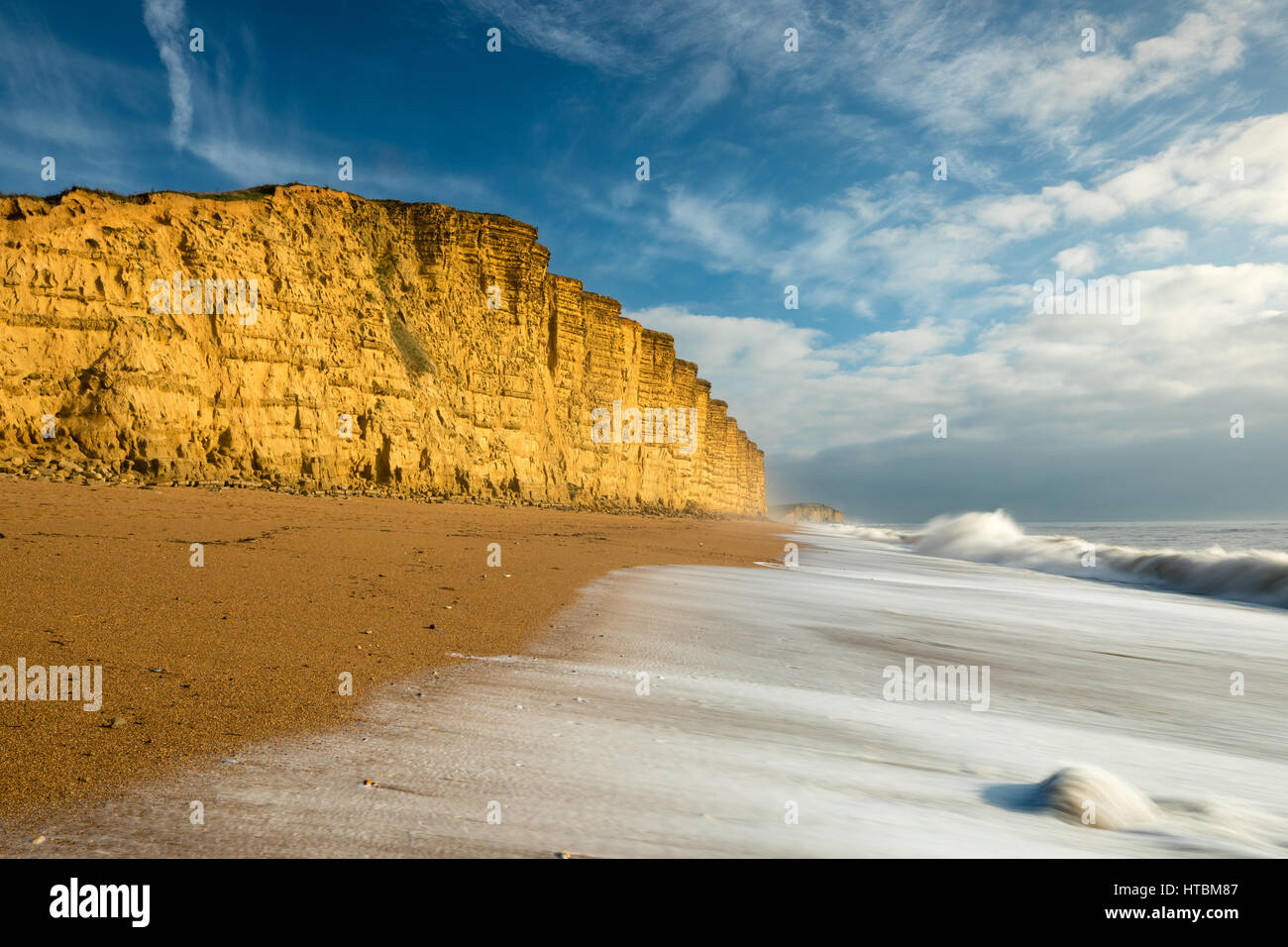 waves breaking on the beach beneath East Cliff, West Bay, Jurassic Coast, Dorset, England, UK Stock Photo