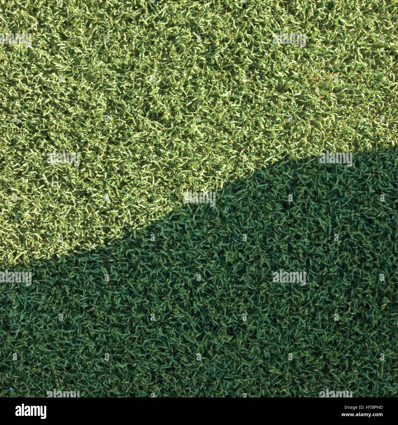 artificial turf texture. Artificial Grass Fake Turf Synthetic Lawn Field Macro Closeup With Gentle Shaded Shadow Area, Green Sports Texture Background A Shade