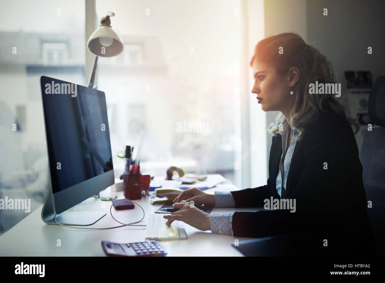 Overworked businesswoman staying in office late to work - Stock Image