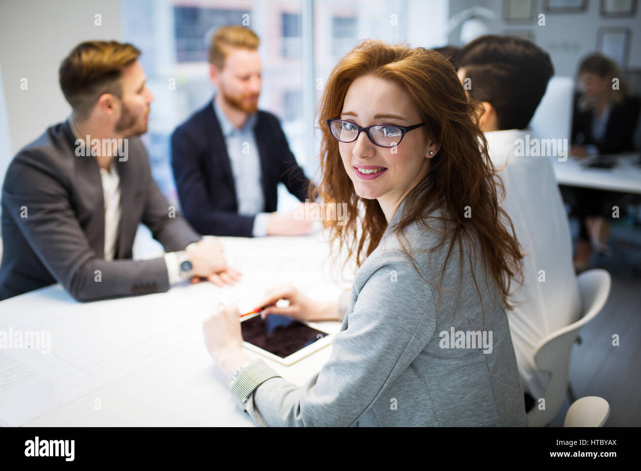 Business colleagues working at their workplace in office - Stock Image