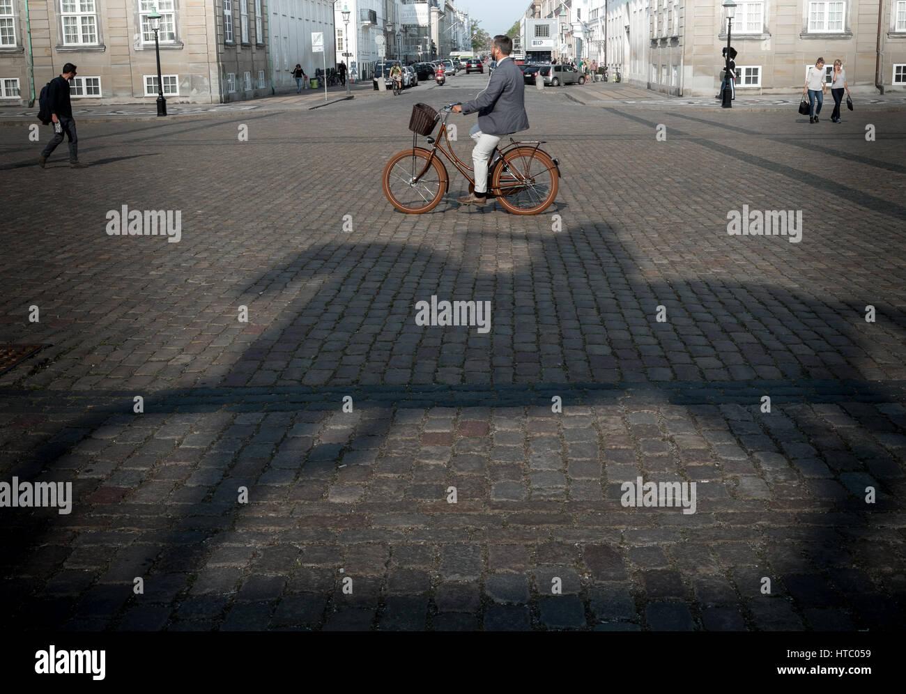 Stylish cyclist passes shadow of the king on horseback, Amalienborg, Copenhagen, Denmark - Stock Image