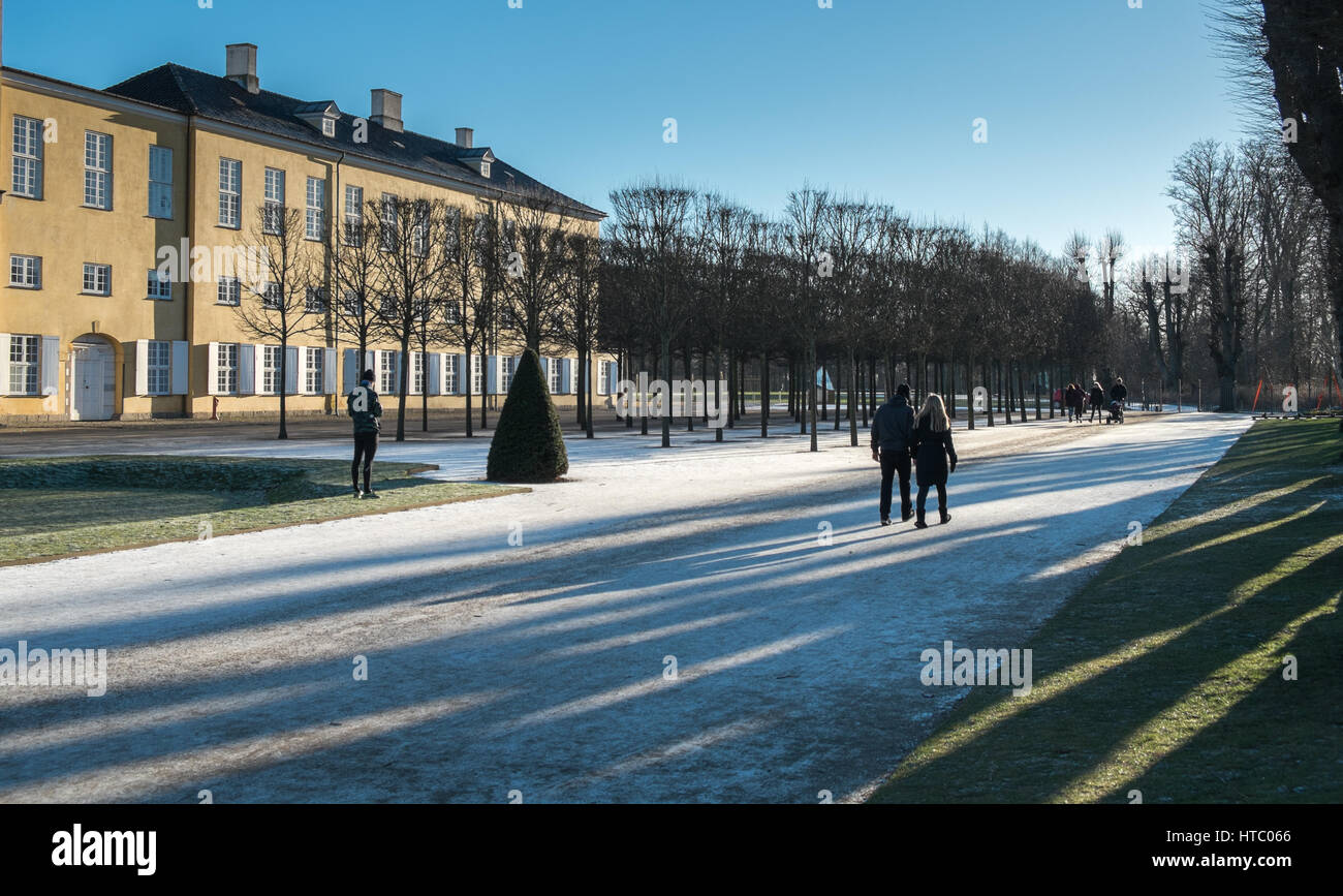 Couple walking in early morning sun at Frederiksberg Slot, Copenhagen, Denmark - Stock Image