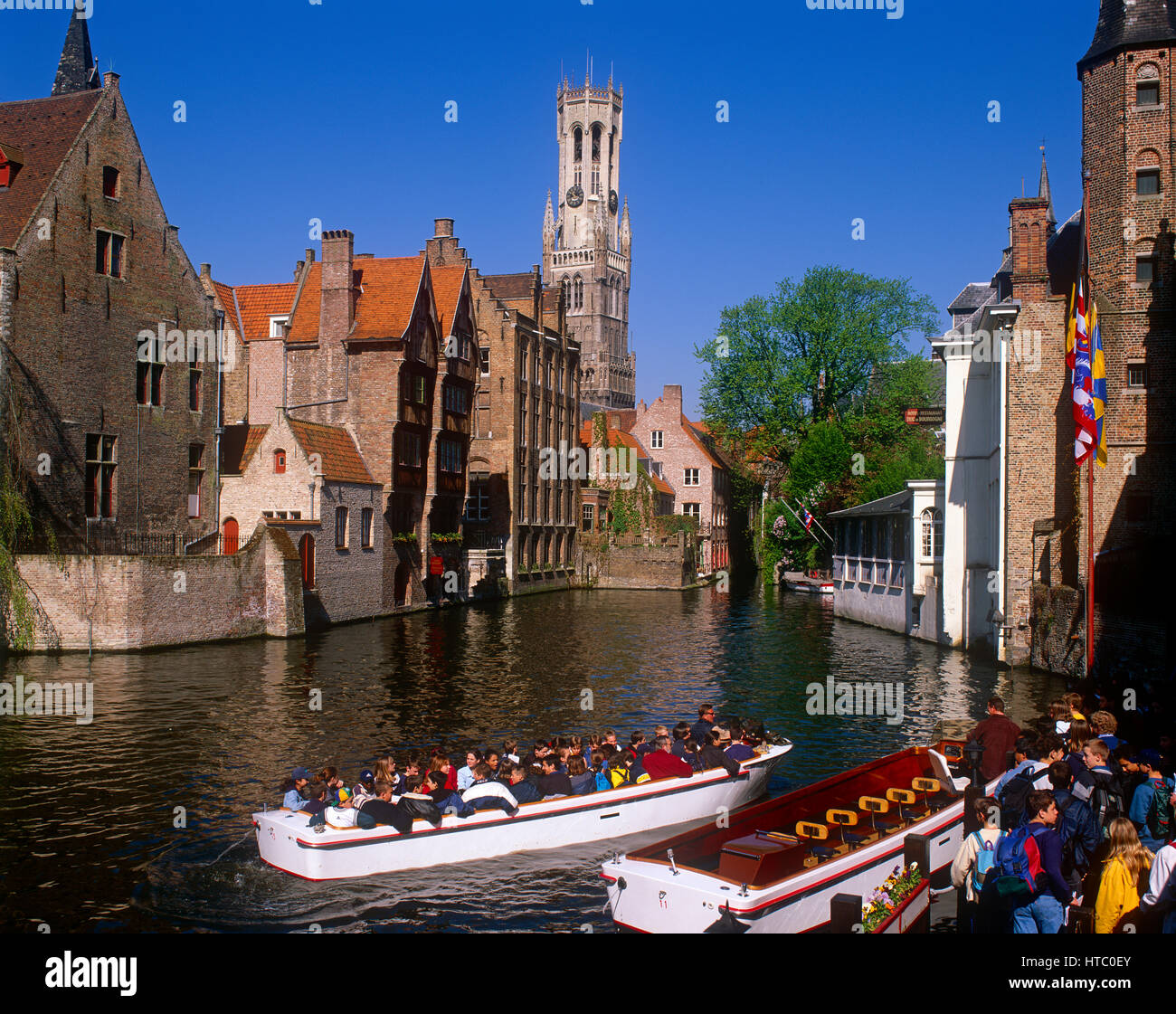 Pleasure boats and tourists on the Dijver Canal with the Belfry in background, Bruges, Belgium. - Stock Image