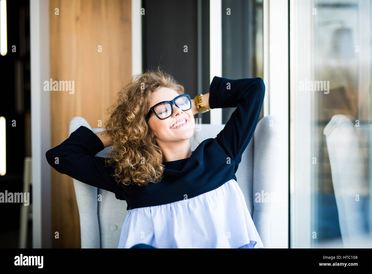 Business woman relaxing working at office desk laid back resting on chair with hands behind head - Stock Image