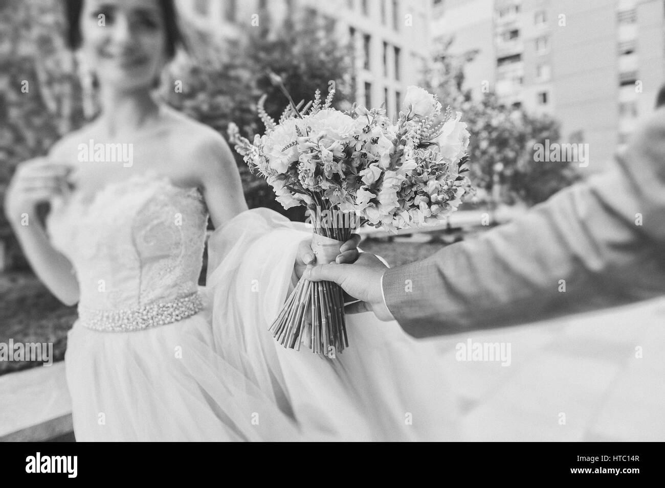 Bride and groom hold a bouquet. Focus on the bouquet. Newly married couple walk on paths holding hands and looking - Stock Image
