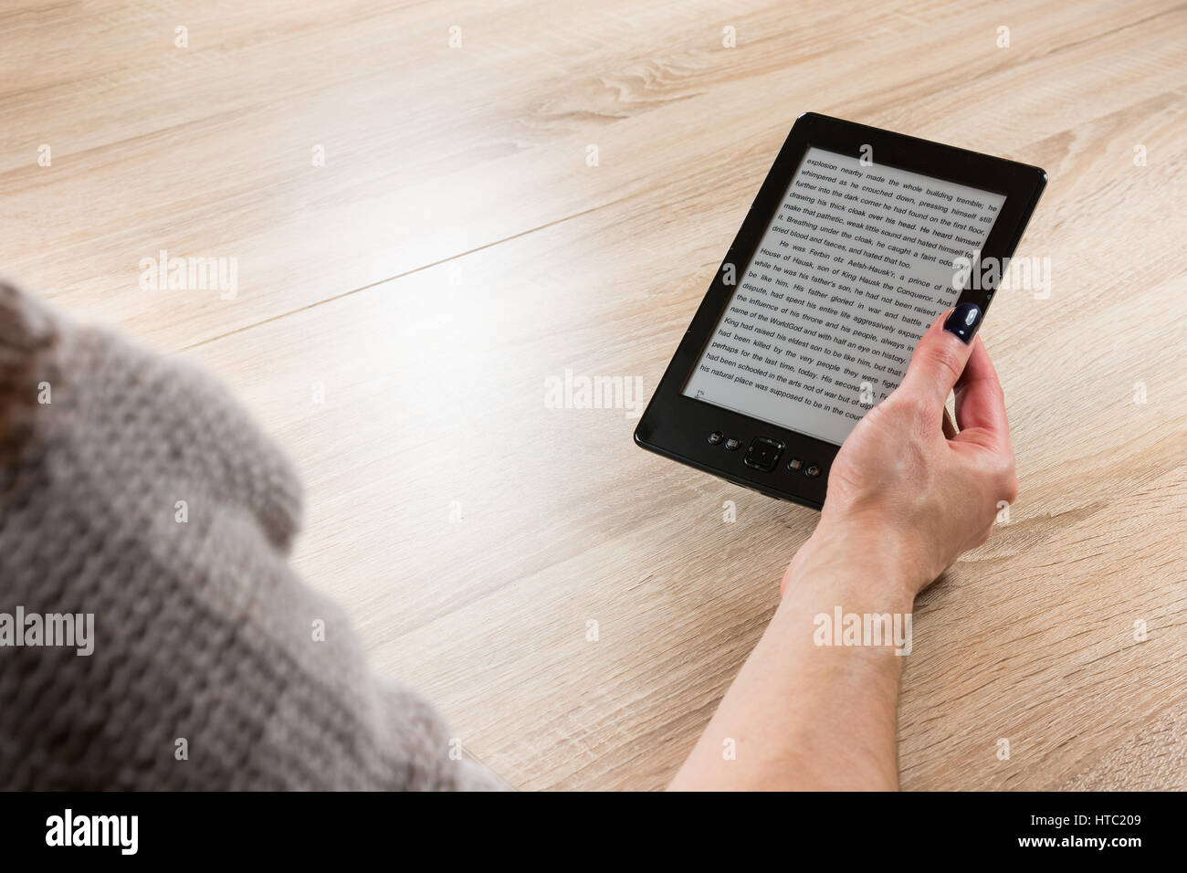 Woman holding ebook reader in front of the table - Stock Image