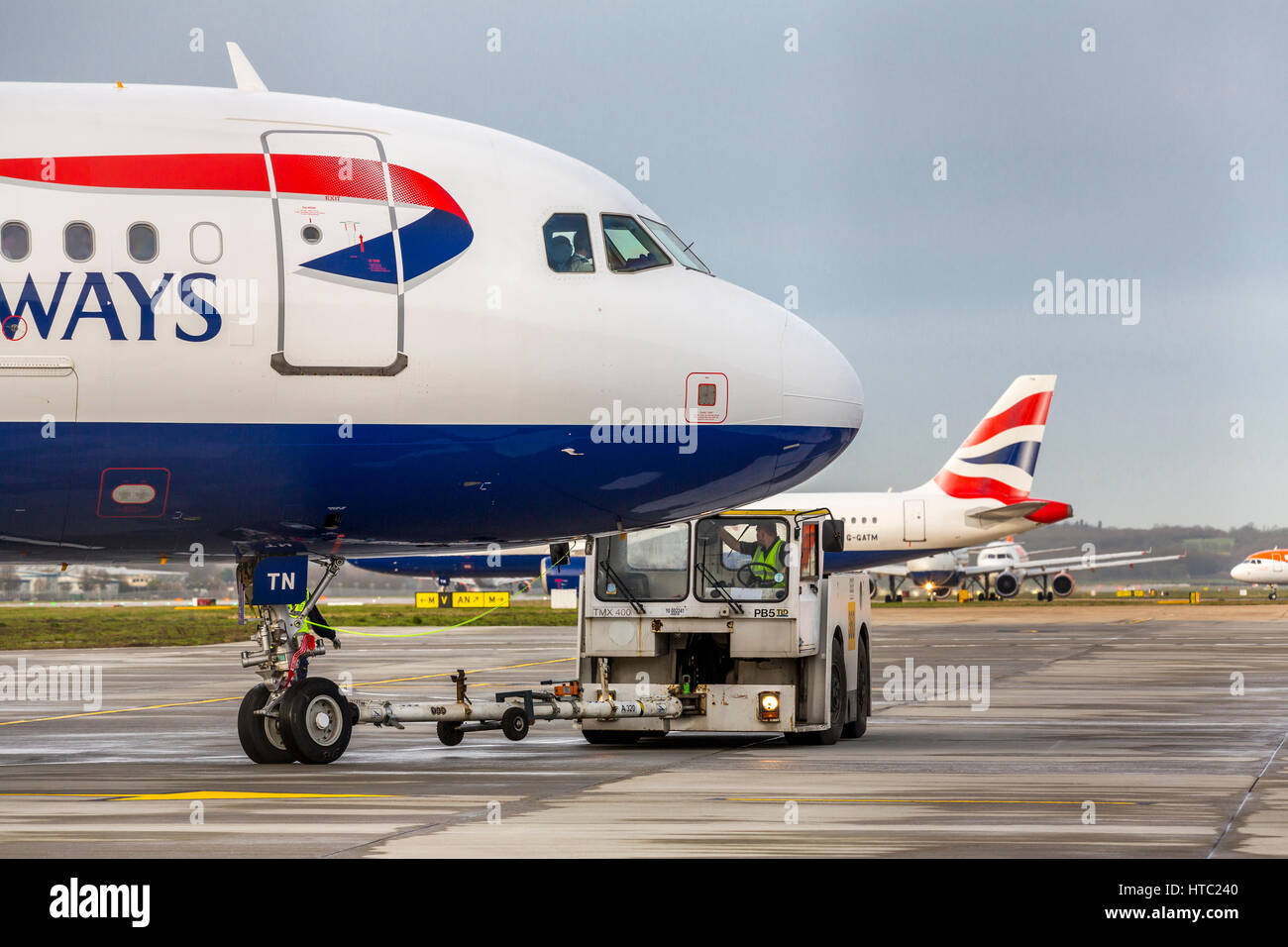 Airbus aircraft towed by a tug taxi for takeoff Gatwick airport  London England UK - Stock Image