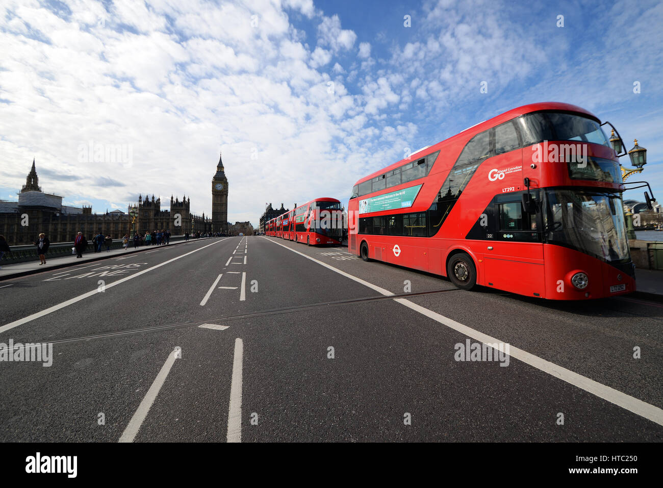 A line of six red New Routemaster London buses on Westminster Bridge, London. Space for copy - Stock Image
