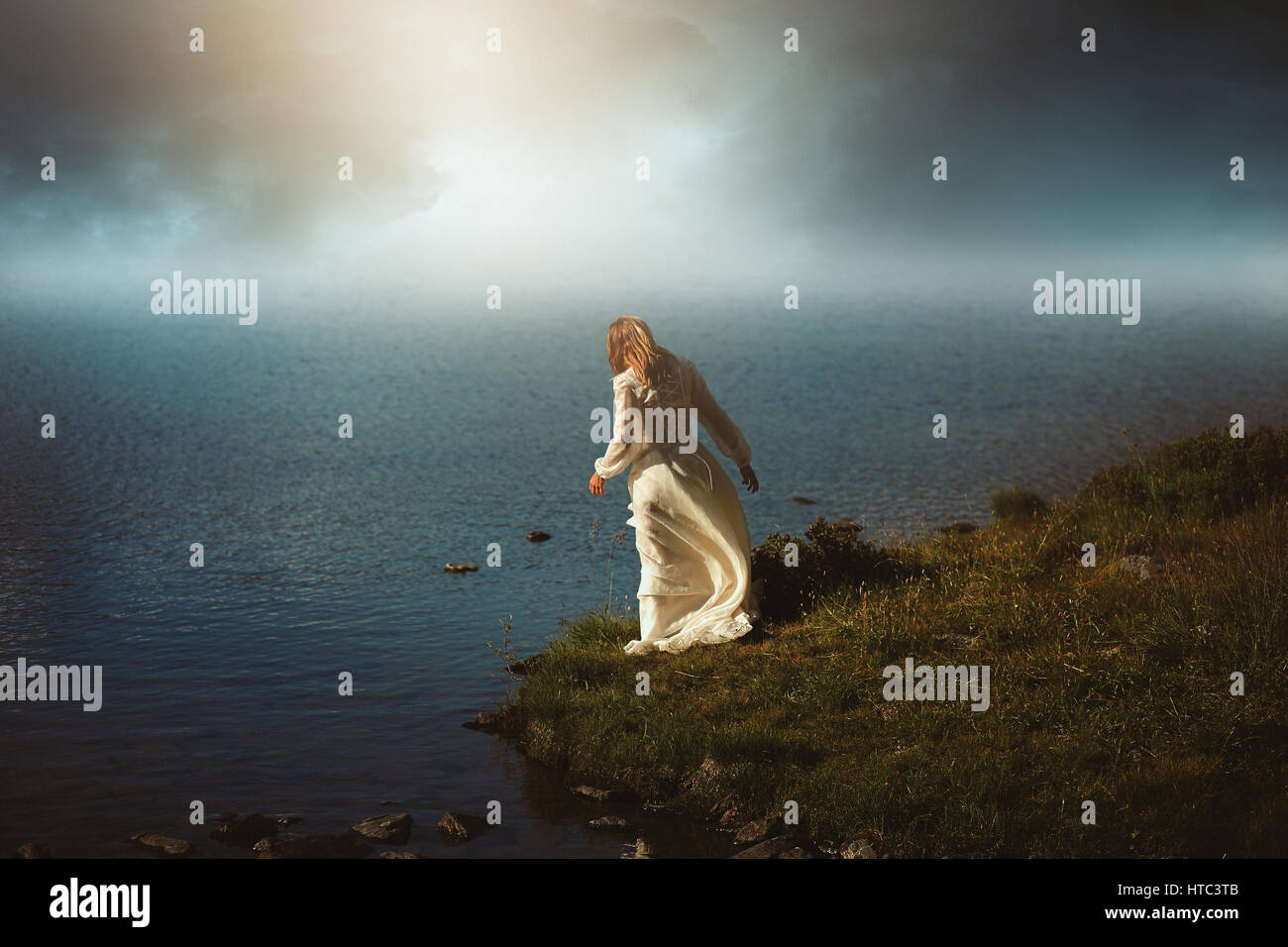Woman looking at surreal waters. Photomanipulation with dreamy colors - Stock Image