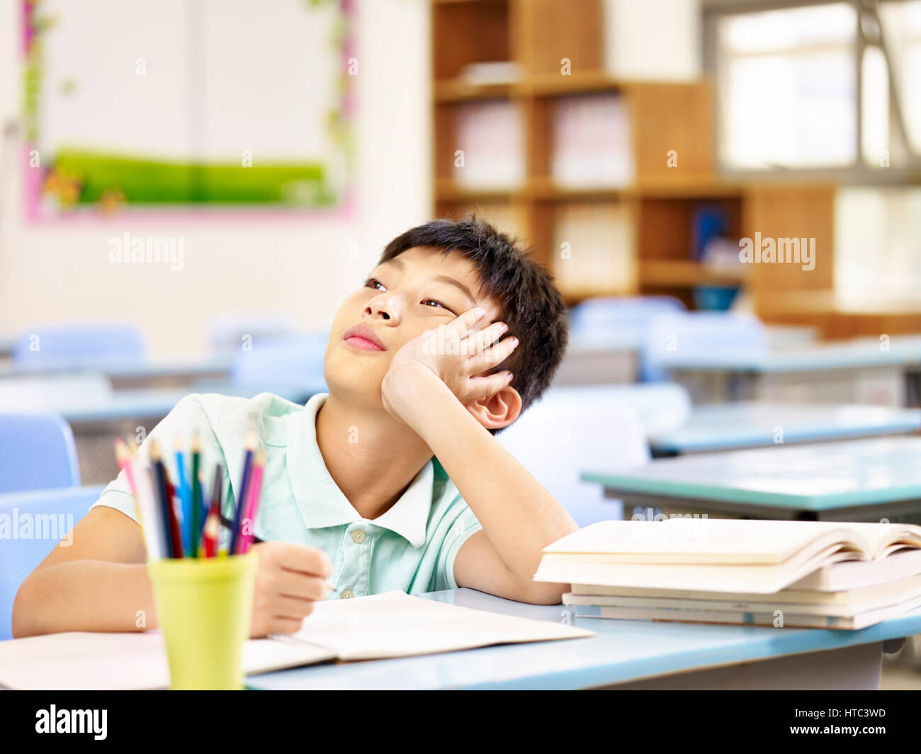 asian elementary schoolboy thinking while doing homework in classroom, looking up hand on cheek. - Stock Image