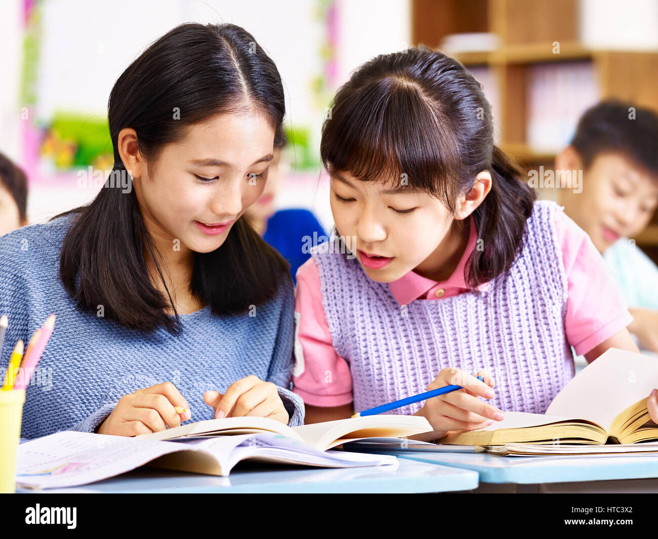 two asian elementary schoolgirls desk mates having a discussion during class in classroom. - Stock Image