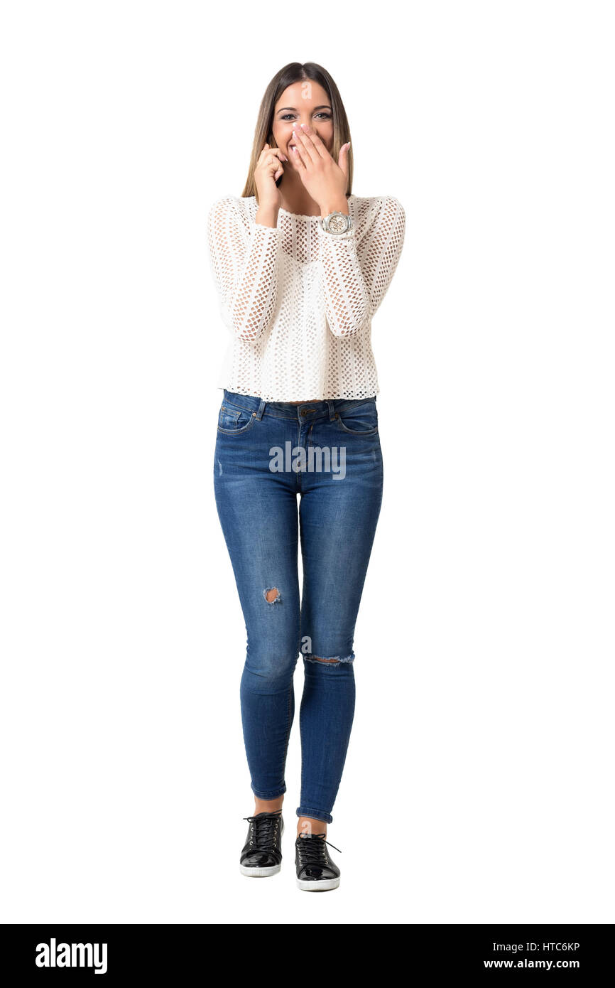 Young casual woman laughing loudly on the phone covering mouth. Full body length portrait isolated over white background. - Stock Image