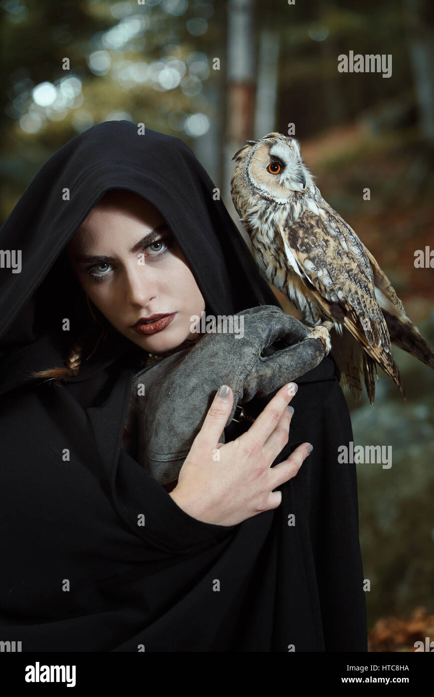 Witch of the forest with her owl friend. Dark fantasy - Stock Image