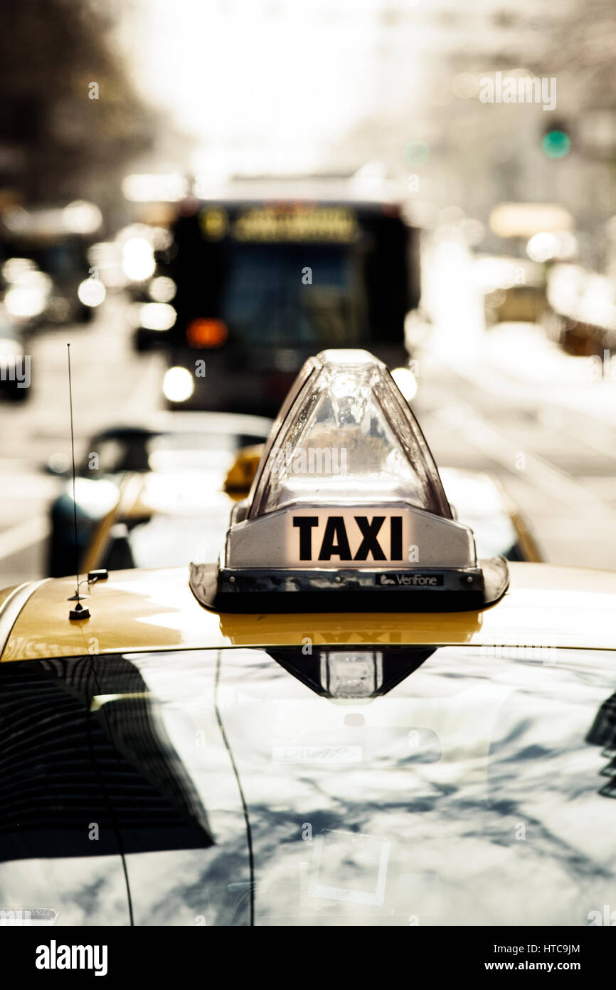 Taxi cab sign with a bus and cars in the background. - Stock Image